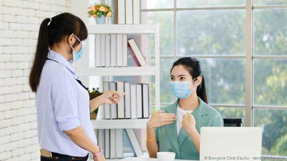Gebärdensprachdolmetscher mit Schutzmaske